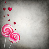 Two colorful lollipops with floating hearts on grunge background — Stock Photo