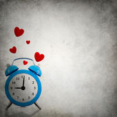 Alarm clock with floating red hearts on grunge background — Stock Photo