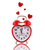 Heart-shaped alarm clock ringing with hearts isolated on white — Stock Photo