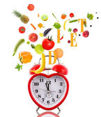 Clock in shape of heart with fruits and vegetables. — Stock Photo