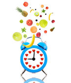 Diet concept, alarm clock ringing,hearts and fruits — Стоковое фото