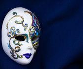 Beautiful mask on heavy dark blue fabric — Stock Photo