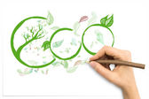 Hand with tree trunk pencil illustrating Eco with leaves  — ストック写真