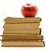 Stack of old books with red apple isolated — Stock Photo