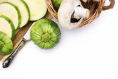 Two round zucchini cut in slices and wicker basket with vegetables isolated on white background — Stock Photo