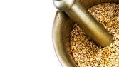 Golden flax seeds inside bronze mortar closeup with copy-space — Stock fotografie