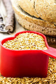 Golden flax seeds with bread and heart closeup — Stock Photo