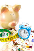 Piggy bank with pile of pills, banknotes clock and measure tape — Stock Photo