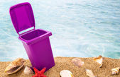 Trash can on clean sand and shells with seascape background  — Stock Photo