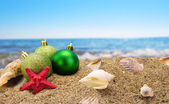 Christmas balls and shells on sand with summer sea background  — Stock Photo
