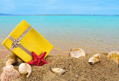 Gold gift box on sand with summer sea background — Stock Photo