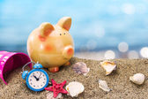 Piggy bank on sand with summer sea background — Stock Photo