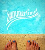 Female feet by the poolside blue waters  — Zdjęcie stockowe