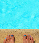 Female feet by the poolside blue waters — Stock Photo