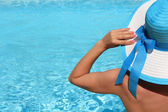 Young lady with white blue hat by the poolside — Stock Photo
