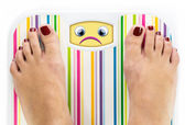 Feet on bathroom scale with sad cute face on dial — Stock Photo