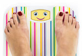 Feet on bathroom scale with smiling cute face on dial — Stock Photo