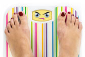 Feet on bathroom scale with angry cute face on dial — Stock Photo