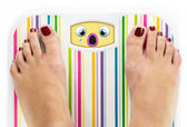 Feet on bathroom scale with crying cute face on dial — Stock Photo