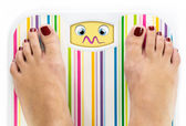 Feet on bathroom scale with overwhelmed cute face on dial — Stock Photo