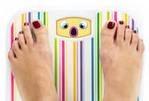 Feet on bathroom scale with scared cute face on dial — Stock Photo