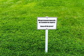 White sign board on green grass — Foto Stock