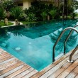 Stock Photo: Small swimming pool with wooden setting surrounded by trees