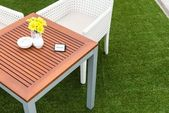 Tropical wooden dinning table on green grass — Stock Photo