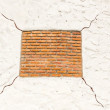 Red square shape brick on white background with cracks — Stock Photo #22231741