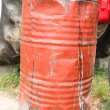 Red dirty rusty and damaged oil drum — Stock Photo