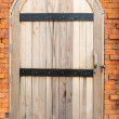 Stock Photo: Vintage old wooden door on a red brick wall