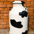 A large multi color metal milk container - Stock Photo