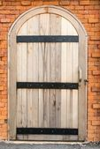 Vintage old wooden door on a red brick wall — Stock Photo