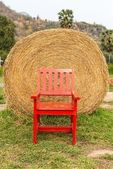 Large rounded hay stack on green grass with red chair — Stock Photo