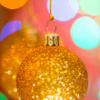 Golden christmas ball on bokeh background — Stock Photo