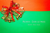 Vintage christmas postcard background with bells andbow — Stock Photo