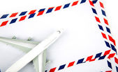 Airmail envelope with model airplane — Stock Photo