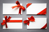 Set of cards with red ribbons bows — Stock Photo