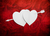 Vintage two paper hearts pierced with an arrow symbol for Valent — Stock Photo