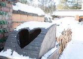 Wooden bin with heart in snow — Photo