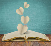Paper cut of heart on old book — Stok fotoğraf