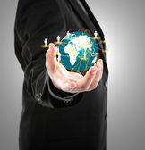 Hombre de negocios sostiene el pequeño mundo en sus manos — Foto de Stock