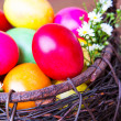 Colorful easter eggs in brown basket with flower — Lizenzfreies Foto