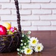 Colorful easter eggs in brown basket with flower — Stock Photo