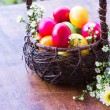 Colorful easter eggs in brown basket with flower - Stock Photo