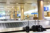 Koffer am flughafen innenraum bei der gepäckausgabe — Stockfoto