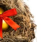 Golden easter eggs in nest isolated on white background — Stock Photo