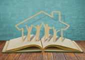 Paper cut family symbol on old book — Stok fotoğraf