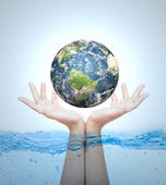 Earth in hand over water (Elements of this image furnished by NA — Stockfoto