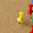 Group of colorful push pins on cork bulletin board. — Stock Photo
